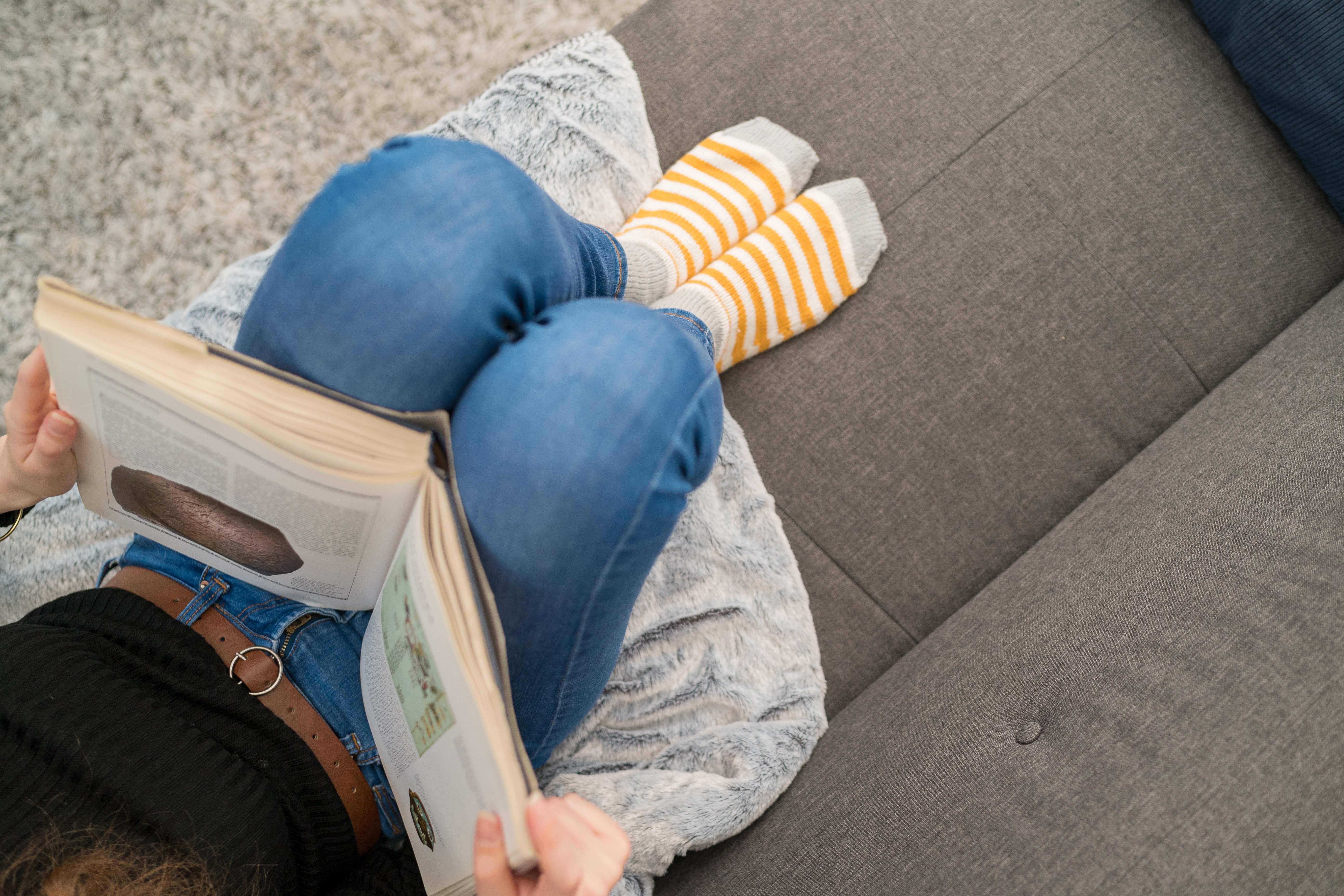 girl sitting on a couch reading a book wearing wool socks